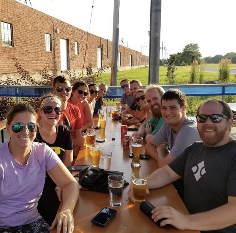 Blue Compass team members drinking beer together.