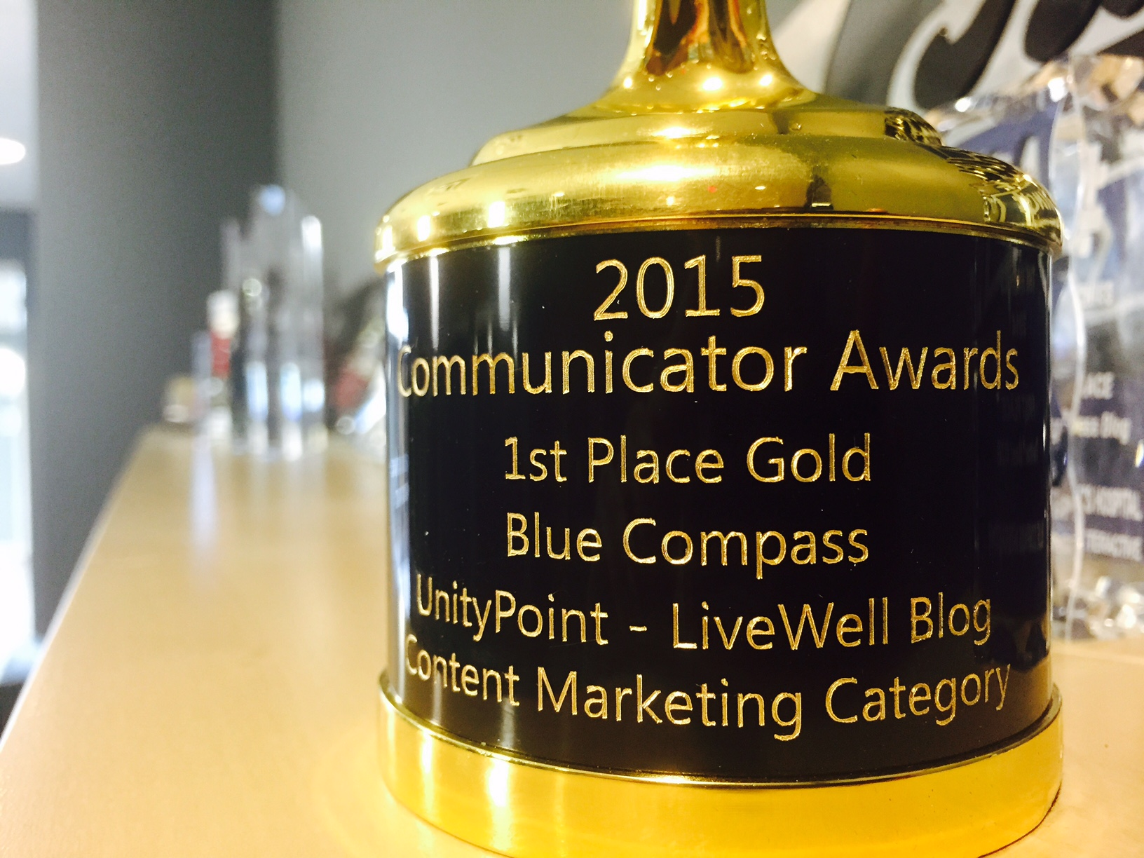Close-up of Blue Compass Gold Excellence Award from The Communicator Awards